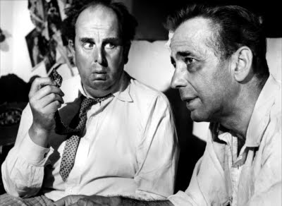 Robert Morley and Humphrey Bogart get down to business in BEAT THE DEVIL