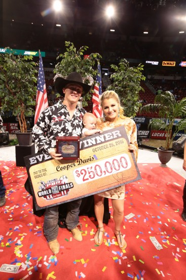 Cooper Davis poses with his wife, Kaitlyn, their son, Mackston, and a big check at the PBR World Finals in Las Vegas (photo by Andy Watson)