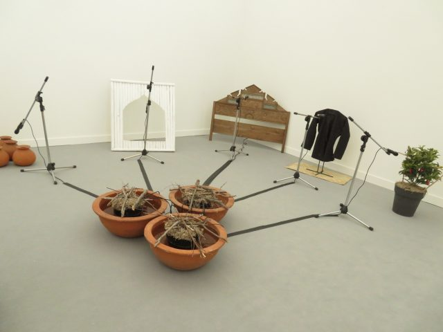 FX Harsono, Voice from the Base of the Dam, wooden panel, bamboo frame, six terracotta jugs, three terracotta pots, Maduranese textile jacket on metal stand, mat, artificial plant, five microphones withh metal stands, speakers, and sound recordings, 1994, Tyler Rollins Fine Art (photo by twi-ny/mdr)