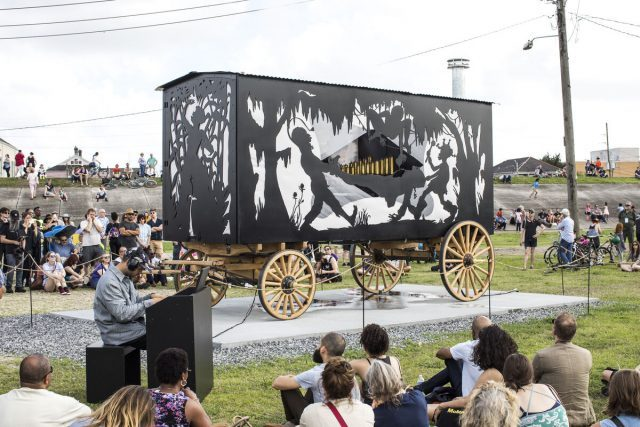 Kara Walker, The Katastwóf Karavan, 2017 (Installation view, Prospect.4: The Lotus in Spite of the Swamp, Prospect New Orleans, New Orleans, Louisiana, 2018). Steel frame mounted to lumber running gear, aluminum, red oak and muslin wall panels, propane fired boiler, water tank, gas generator, brass and steel 38-note steam calliope, calliope controller panel with MIDI interface, iPad controller with QRS PNO software; 152 × 216 × 100 inches (386.1 × 548.6 × 254 cm). © Kara Walker. Image courtesy Sikkema Jenkins & Co., New York. Photograph by Alex Marks