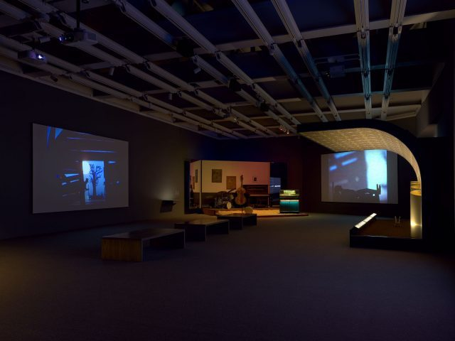 Installation view of Jason Moran (Whitney Museum of American Art, New York, September 20, 2019-January 5, 2020). Projections: Kara Walker, National Archives Microfilm M999 Roll 34: Bureau of Refugees, Freedmen and Abandoned Lands: Six Miles from Springfield on the Franklin Road, 2009. Stages from left to right: Jason Moran, STAGED: Slugs' Saloon, 2018; Jason Moran, STAGED: Savoy Ballroom 1, 2015. Photograph by Ron Amstutz
